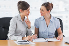 Smiling businesswomen working together on documents Stock Images