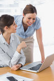 Smiling businesswomen working together with laptop Royalty Free Stock Photo