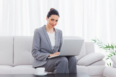 Smiling busineswoman sitting on sofa using laptop Royalty Free Stock Image