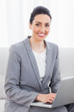 Smiling busineswoman using laptop sitting on sofa Royalty Free Stock Photography
