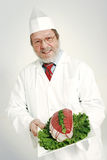 Smiling Butcher. A portrait of smiling elderly butcher holding a rosbeef piece in a white plate stock photo