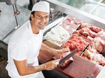 Smiling Butcher Cutting Meat At Counter Stock Image