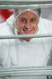 Smiling butcher standing in meat factory Royalty Free Stock Photos
