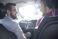 Smiling buyer and dealer during a test drive in a exclusive car. Concept photo stock images