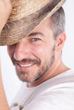 Smiling cacasian man with a beard lifting a hat Royalty Free Stock Image