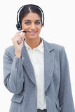 Smiling call center agent adjusting microphone Royalty Free Stock Image