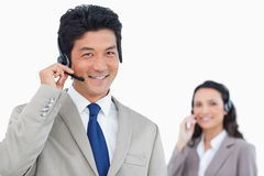 Smiling call center agent with colleague behind him Stock Image