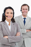 Smiling call center agents with headsets and arms folded Royalty Free Stock Images
