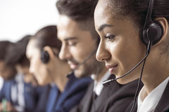 Smiling call center operator in headset working with colleagues behind stock images
