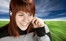 Smiling call center redhead. Beautiful smiling girl at a call center answering with a handset. Studio shot stock photography