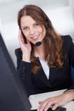 Smiling call center worker sitting typing Royalty Free Stock Images