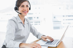 Smiling call centre agent working at desk Royalty Free Stock Photos