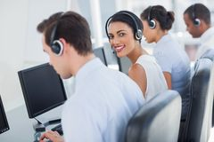 Smiling call centre employee looking over shoulder. While having a discussion Stock Photos