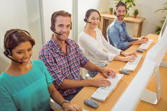 Smiling call centre team looking at the camera Stock Photo