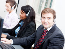 Smiling callcenter agent with headset support Stock Photos