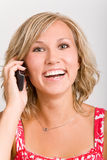 Smiling and calling. Blonde woman laughing on the phone royalty free stock image