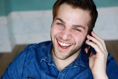 Smiling and calling on mobile phone. Close up portrait of a young man smiling and calling on mobile phone Stock Photos