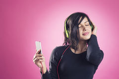 Smiling calm girl enjoying listening to music with earphones. Royalty Free Stock Images