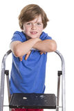 Smiling for the camera. Young boy leaning on a ladder with arms crossed, smiling at the camera, in the studio Royalty Free Stock Image