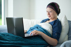 Smiling cancer girl using laptop stock images