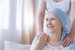 Smiling cancer woman with daughter. Smiling cancer women with daughter keeping hands on her arms Stock Photo