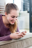 Smiling candid beautiful teenage girl typing on her smartphone Stock Photo