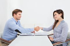 Smiling candidate shaking hand with businessman royalty free stock photo