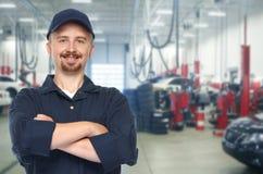 Smiling car mechanic in auto repair service. Stock Photo