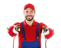 Smiling car mechanic with jumper cables isolated on white. Background Royalty Free Stock Images