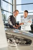 Smiling car salesman with customer stock images