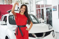 Smiling car salesman handing over your new car keys, dealership and sales concept. Happy girl the buyer.  Royalty Free Stock Photo