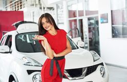 Smiling car salesman handing over your new car keys, dealership and sales concept. Happy girl the buyer Stock Photography