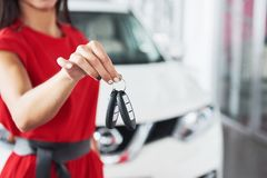 Smiling car salesman handing over your new car keys, dealership and sales concept. Happy girl the buyer.  Stock Image