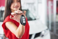 Smiling car salesman handing over your new car keys, dealership and sales concept. Happy girl the buyer.  Stock Photo