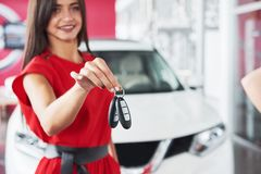 Smiling car salesman handing over your new car keys, dealership and sales concept. Happy girl the buyer.  Stock Photos