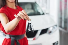Smiling car salesman handing over your new car keys, dealership and sales concept. Happy girl the buyer.  Royalty Free Stock Image