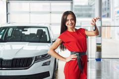 Smiling car salesman handing over your new car keys, dealership and sales concept. Happy girl the buyer Royalty Free Stock Image