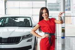 Smiling car salesman handing over your new car keys, dealership and sales concept. Happy girl the buyer Royalty Free Stock Photos