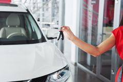 Smiling car salesman handing over your new car keys, dealership and sales concept. Happy girl the buyer Stock Photos