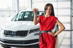 Smiling car salesman handing over your new car keys, dealership and sales concept. Happy girl the buyer Royalty Free Stock Images