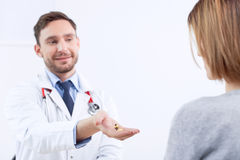 Smiling cardiologist giving pills to the patient. Helpful hand. Nice doctor giving pills to  patient while sitting at the table and talking to her Royalty Free Stock Photo