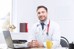 Smiling cardiologist sitting at the table Royalty Free Stock Photography