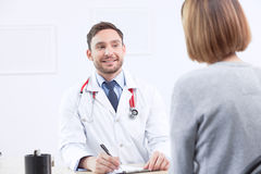 Smiling cardiologist talking to the patient Stock Photography