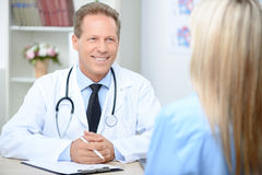 Smiling cardiologist talking to the patient. How do you feel. Pleasant content professional doctor holding pan and sitting at the table while talking with Royalty Free Stock Photo
