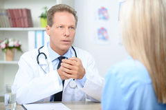 Smiling cardiologist talking to the patient. I will cure you. Serious agreeable professional doctor holding hands together and sitting at the table while Stock Image