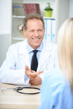 Smiling cardiologist talking to the patient. I will help you. Pleasant smiling delighted doctor sitting at the table and evincing joy while  talking with patient Stock Image