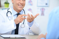 Smiling cardiologist talking to the patient. Lets see. Pleasant cheerful professional doctor folding his fingers and sitting at the table while talking with his Royalty Free Stock Photos
