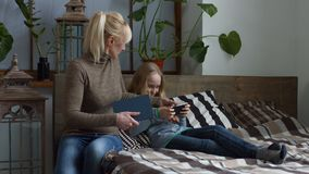 Strict mother making her daughter to do homework. Smiling carefree little blonde girl playing on mobile phone while lying on the bed. Strict adult mother taking stock video