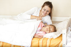 Smiling careful mother covering daughter with blanket Royalty Free Stock Photography