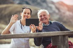 Smiling caregiver nurse and  disabled senior patient using digital tablet. Outdoor Royalty Free Stock Image
